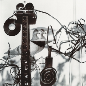 A black-and-white photograph of parts of an unspooled cassette tape and recording devices sitting on top of an image of pigeons, with dramatic shadows cast by the devices