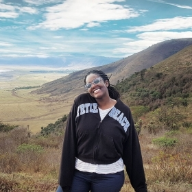 Thanda Newkirk '21 stands with the Tanzanian mountain landscape behind her