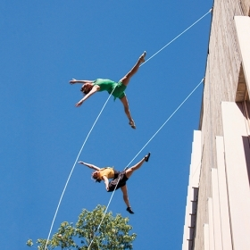 Two dancers swing from ropes attached to the new Pendleton West building